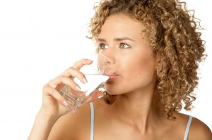 Portrait of young woman drinking water